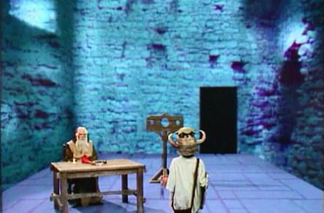 Knightmare Series 4 Quest 2. Merlin is sat at a table in Level 2.